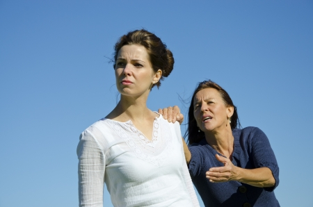 Mother and daughter having an argument  Daughter is trying to get away and mother is holding her back  Clear blue sky and copy space