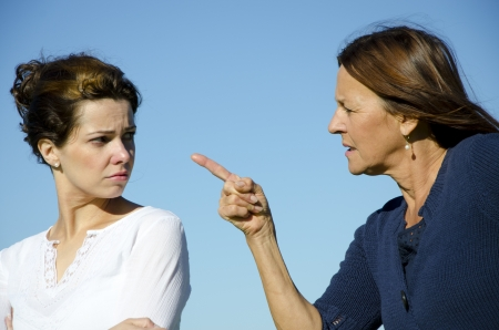 Two attractive women, mother and daughter discussing, fighting, communicating Clear blue sky