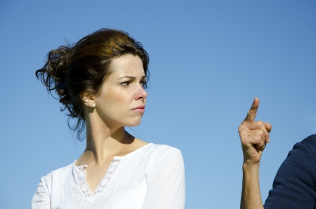 accusation: Pretty young woman with angry facial expression looking back at an in accusation pointed arm  Clear blue sky and copy space  Stock Photo