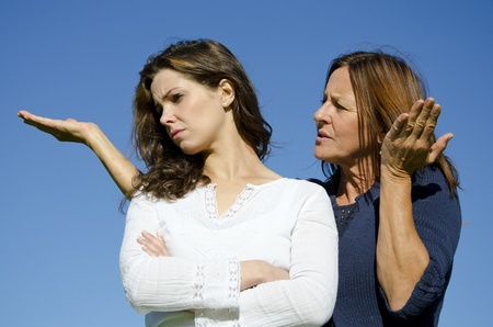Mother discussing with her ignoring and stubborn looking daughter who turned her back on her