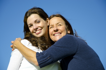 brown haired: Beautiful mother and daughter hugging each other on a sunny  day outside, with clear blue sky as background and copy space
