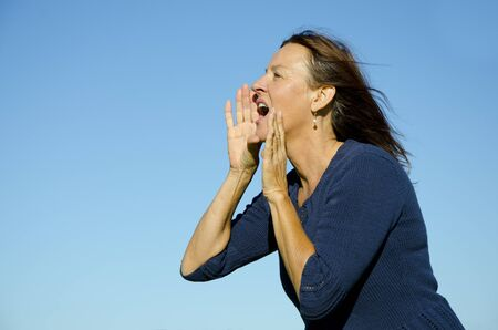 woman shouting: Attractive mature woman with brown hair shouts out loud at a sunny remote outdoor scenery with blue sky background and copy space