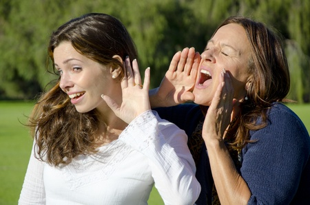 deafness: Communication between two women, between two generations, mother and daughter, two friends, one shouting, one listening, in front of a blurred green forest background