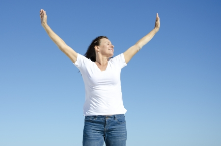 An attractive looking mature woman in her fifties showing her happy feelings by rising her arms up in the air, with a friendly smile and closed eyes, clear blue sky as background and copy space. photo