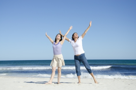 at ease: Two generations, two women, mother and daughter are happy together at the beach, in a cheerful mood with their arms up in the air, wide open ocean and clear blue summer sky as background and copy space.
