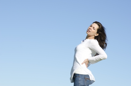 A beautiful looking young woman is suffering from back pain, with stressful facial expression, clear blue sky as background and copy space. Stock Photo - 14213271