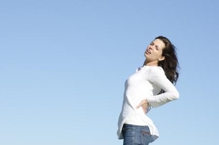 Una bella donna cerca giovane soffre di mal di schiena, con stressante espressione facciale, un cielo azzurro come sfondo e lo spazio della copia.
