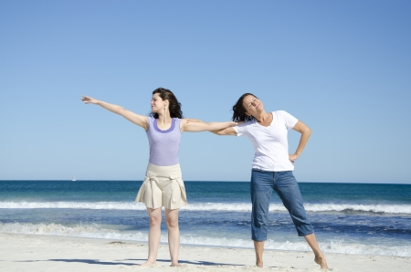 Mother and daughter, two generations, on the beach, having fun, showing affection and love and happiness, with wide open ocean, clear blue sky as background and copy space. photo