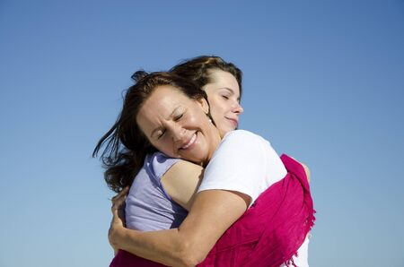 Feeling good, feeling happy: two women, two generations, mother and daughter holding each other in a cuddle, with clear blue sky as background and copy space. photo
