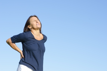 A middle aged woman with back ache problems and a painful facial expression. Clear blue sky as background and copy space.