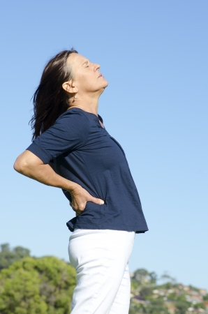 An attractive looking middle aged woman having back problems, feeling the pain in her body, with her eyes closed. Blue sky as background and copy space. photo