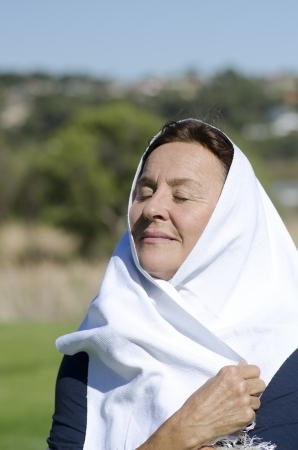 middle eastern clothes: Isolated portrait of mature muslim woman with white fabric around her head, looking relaxed and contemplating with closed eyes, blurred background and copy space