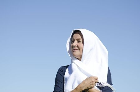 purdah: Isolated portrait of mature muslim woman with white fabric around her head, looking relaxed and contemplating, clear blue sky as background and copy space
