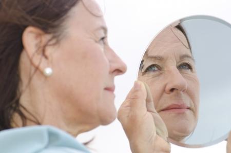 arrugas: Retrato de una atractiva mujer de mediana edad que mira en un espejo, con enfoque en la posición de la imagen espejo