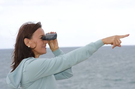 Attractive looking mature woman looking through binoculars and point with one arm, happy, optimistic, confident  Isolated with ocean and white sky as background and copy space