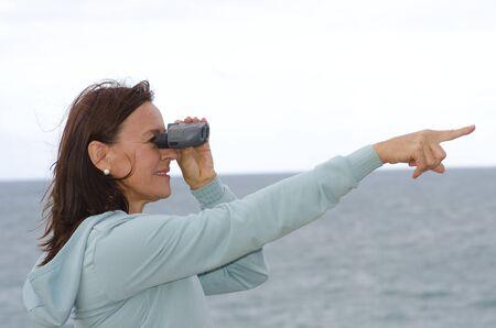 Attraente donna in cerca maturo, guardando attraverso il binocolo e il punto con un braccio, felice, ottimista, fiducioso Isolato con mare e cielo come sfondo bianco e copia spazio Archivio Fotografico