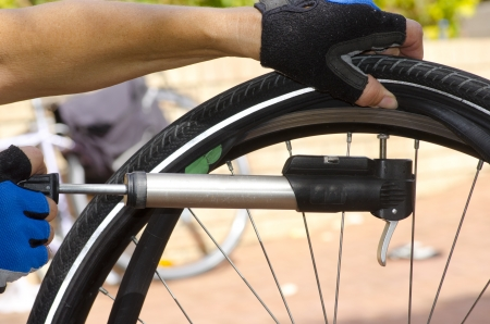 flat tyre: Detail image of bike repair, changing tyre, tube and valve, with blurred background  Stock Photo