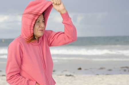 mature woman: Lonely mature woman standing at the beach, keeping herself warm, isolated with ocean and dark storm clouds as background and copy space  Stock Photo