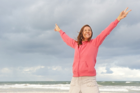 Positive, optimistic mature woman, with happy smile and arms up, isolated with beach, ocean and storm clouds as background and copy space