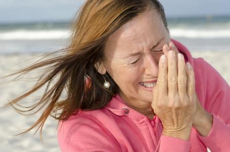 Donna triste e depressa all'aperto in spiaggia, isolata con l'oceano come sfondo sfocato