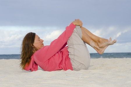 Attractive mature woman exercising at beach, isolated with ocean and storm clouds as background and copy space  photo