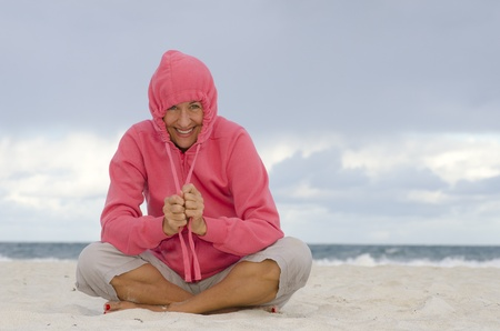 Portrait happy, positive and attractive looking mature woman keeping herself warm at a stormy day at the beach, isolated with ocean and dark clouds as background and copy space  photo