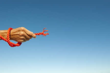 Hand on cut off orange rope isolated with blue sky as background and copy space  photo