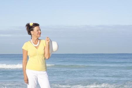 Relaxed and attractive looking senior woman standing happy at the beach, enjoying retirement, isolated with ocean and sky as background and copy space Stock Photo - 15376904