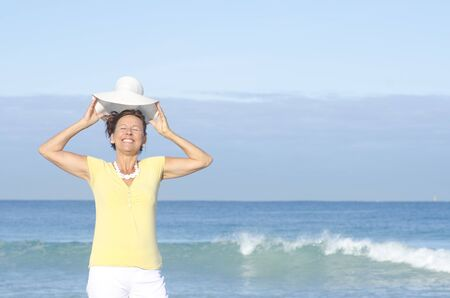 Relaxed and attractive looking senior woman standing happy at the beach, enjoying retirement, isolated with ocean and sky as background and copy space  Stock Photo - 15376684