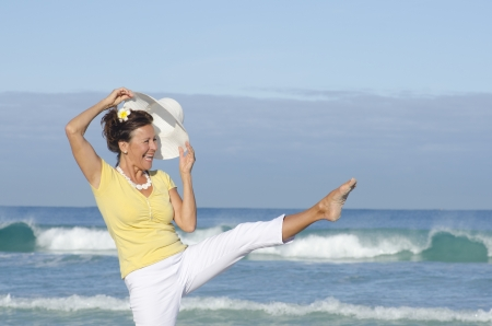 Happy healthy retired woman at the beach, stretching one leg in the air, cheerful laughing, isolated with ocean and sky as background and copy space Stock Photo - 15376802