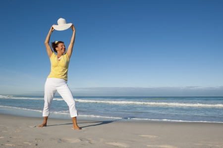 Cheerful happy and attractive looking senior woman enjoying retirement at beach, isolated with ocean and sky as background and copy space Stock Photo - 15376574