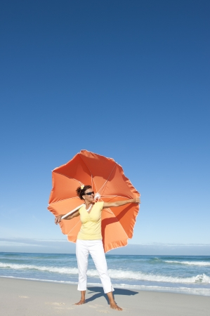 Beautiful looking senior woman standing happy and cheeful with big orange umbrella at beach enjoying retirement, isolated with ocean and blue sky as background and copy space  Stock Photo - 15376566