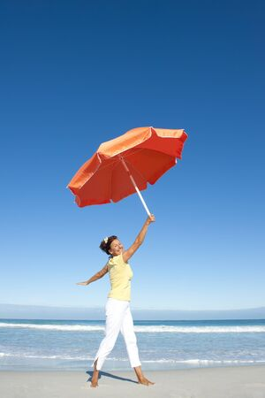 A pretty looking mature woman dancing happy and cheerful with big orange umbrella at beach, isolated with ocean and blue sky as background and copy space  photo