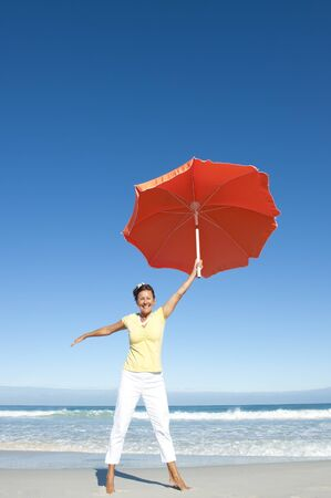 A pretty looking mature woman dancing happy and cheerful with big orange umbrella at beach, isolated with ocean and blue sky as background and copy space