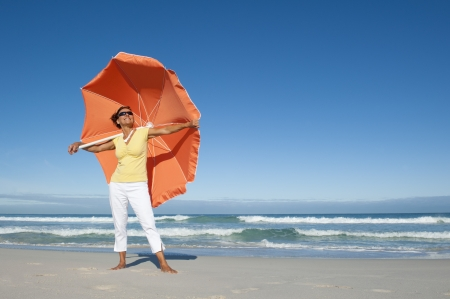 Beautiful looking senior woman standing happy and cheeful with big orange umbrella at beach enjoying retirement, isolated with ocean and blue sky as background and copy space. photo