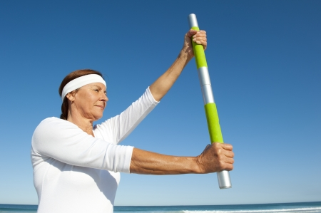 Portrait of attractive and active senior woman doing exercises with hand gripped around weight, isolated with ocean and blue sky as background and copy space. photo