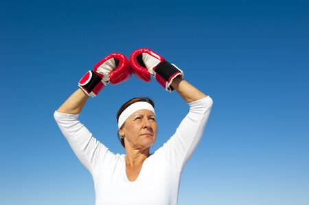 Attractive active senior woman exercising with boxing gloves, posing confident and focused, isolated with blue sky as background and copy space. photo
