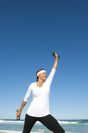 Attractive and active senior woman exercising with weights at the beach, with ocean and blue sky as background and copy space. Stock Photo - 15376557