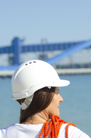 female construction worker: Portrait Female construction worker wearing safety helmet and wearing orange rope over shoulder, isolated with industrial plant and sky as blurred background and copy space.