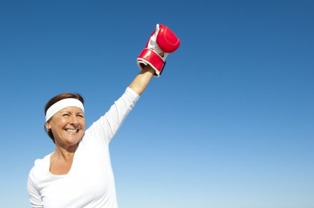Attractive and active senior woman in victory pose with boxing glove, feeling confident and fit after exercising, isolated with blue sky as background and copy space.