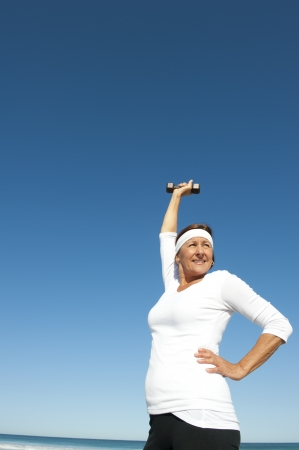 Attractive and active senior woman exercising with weights at the beach, with ocean and blue sky as background and copy space. photo