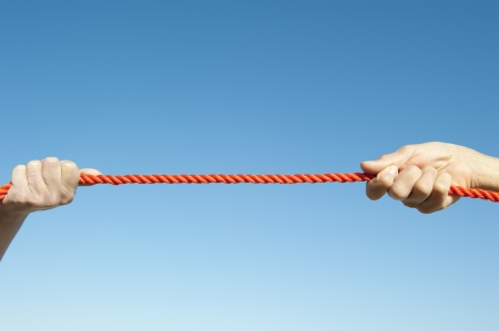 disharmony: Two hands gripped around orange rope and pulling in contest, isolated with blue sky as background and copy space. Stock Photo