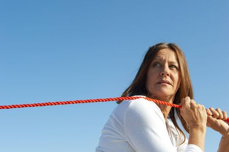 Attratcive mature woman with confident look is pulling stretched orange rope over one shoulder, isolated with blue sky as background and copy space. photo