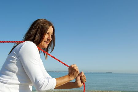 woman rope: Attratcive mature woman with confident look is pulling stretched orange rope over one shoulder, isolated with ocean and blue sky as background and copy space.
