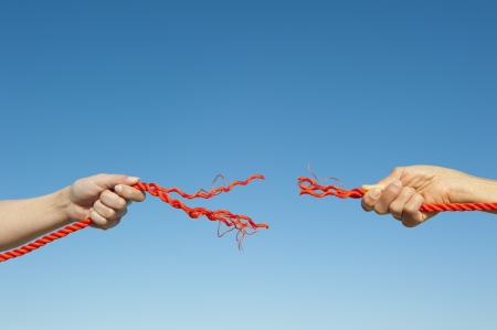 disconnection: Two hands gripped around broken orange rope leaving a gap, isolated with blue sky as background and copy space. Stock Photo