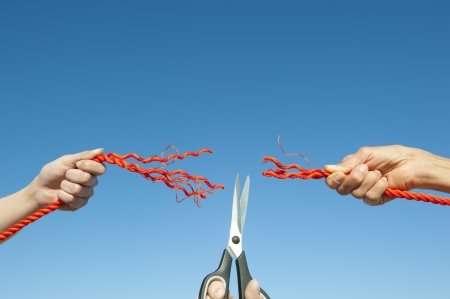 cut the competition: Hands on cut rope, disconnected, with scissors in centre, isolated with blue sky as background and copy space. Stock Photo
