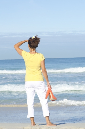 Attractive woman standing alone at beach looking over ocean, with high heel shoes in hand, isolated with sea and sky as background and copy space. photo
