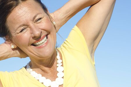 serenety: Portrait of positive and optimistic attractive senior woman with arms behind neck, isolated with blue sky as background and copy space.
