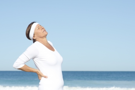 Active and attractive looking senior woman suffering backpain, isolated with blue sky and ocean as background and copy space.