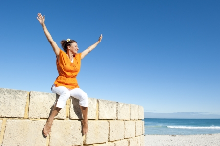 Active and attractive senior woman happy sitting on top of wall, smiling and relaxed, isolated with blue sky and ocean as background and copy space.